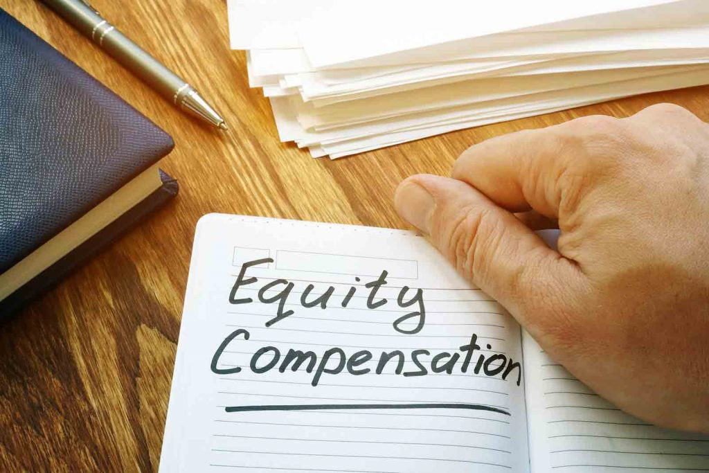 "Holding a notebook reading ""Equity Compensation"""