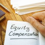 """Holding a notebook reading """"Equity Compensation"""""""
