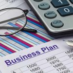 Business plan image with a calculator, glasses, pen and paper with facts and figures on it