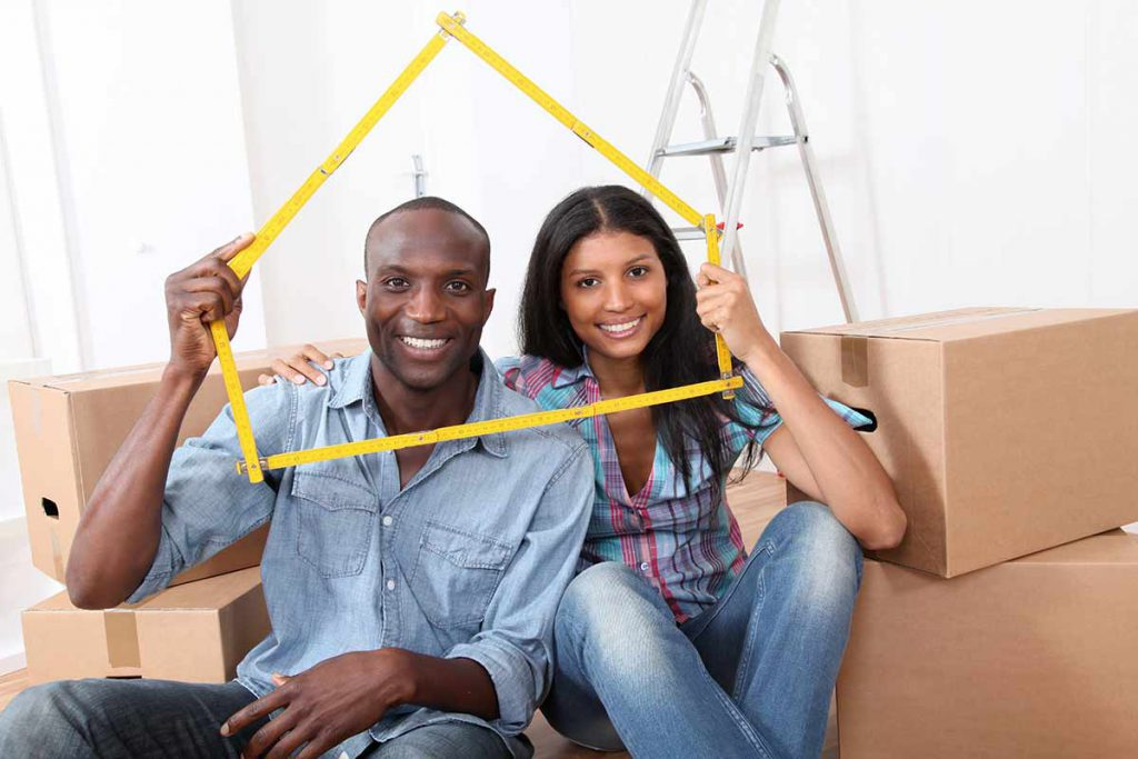 african american couple sitting in what looks like a room of a new house as it is filled with boxes.