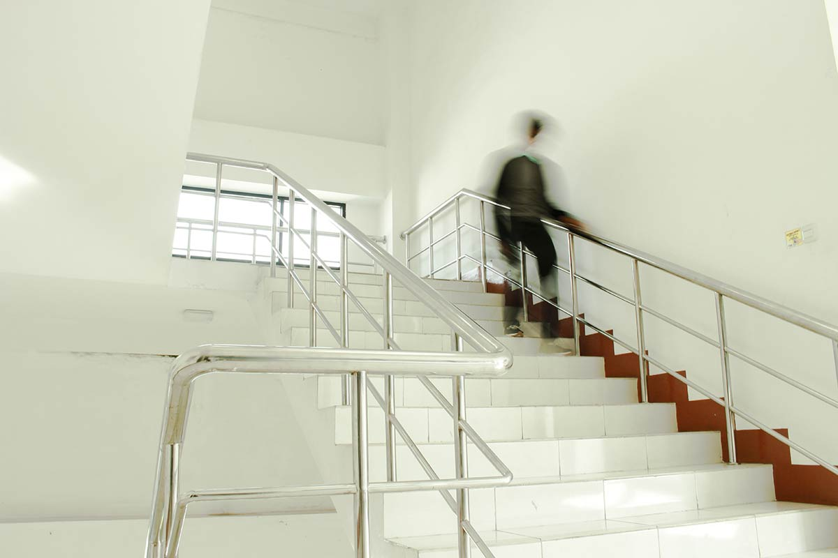 A person walking down a flight of stairs in an apartment complex showing a potential for a slip and fall accident.