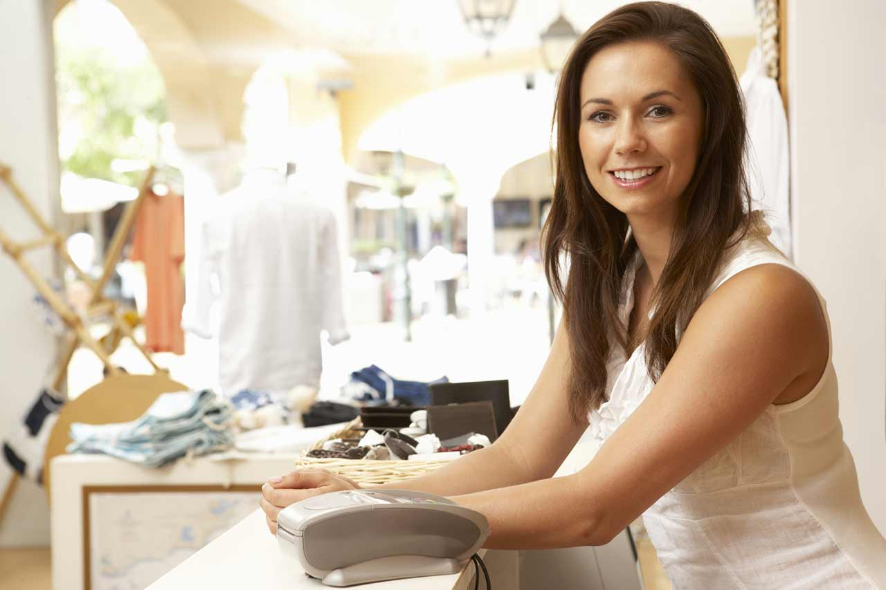 Smiling woman leaning on her desk indicating that she's preparing her estate planning for small business owners.
