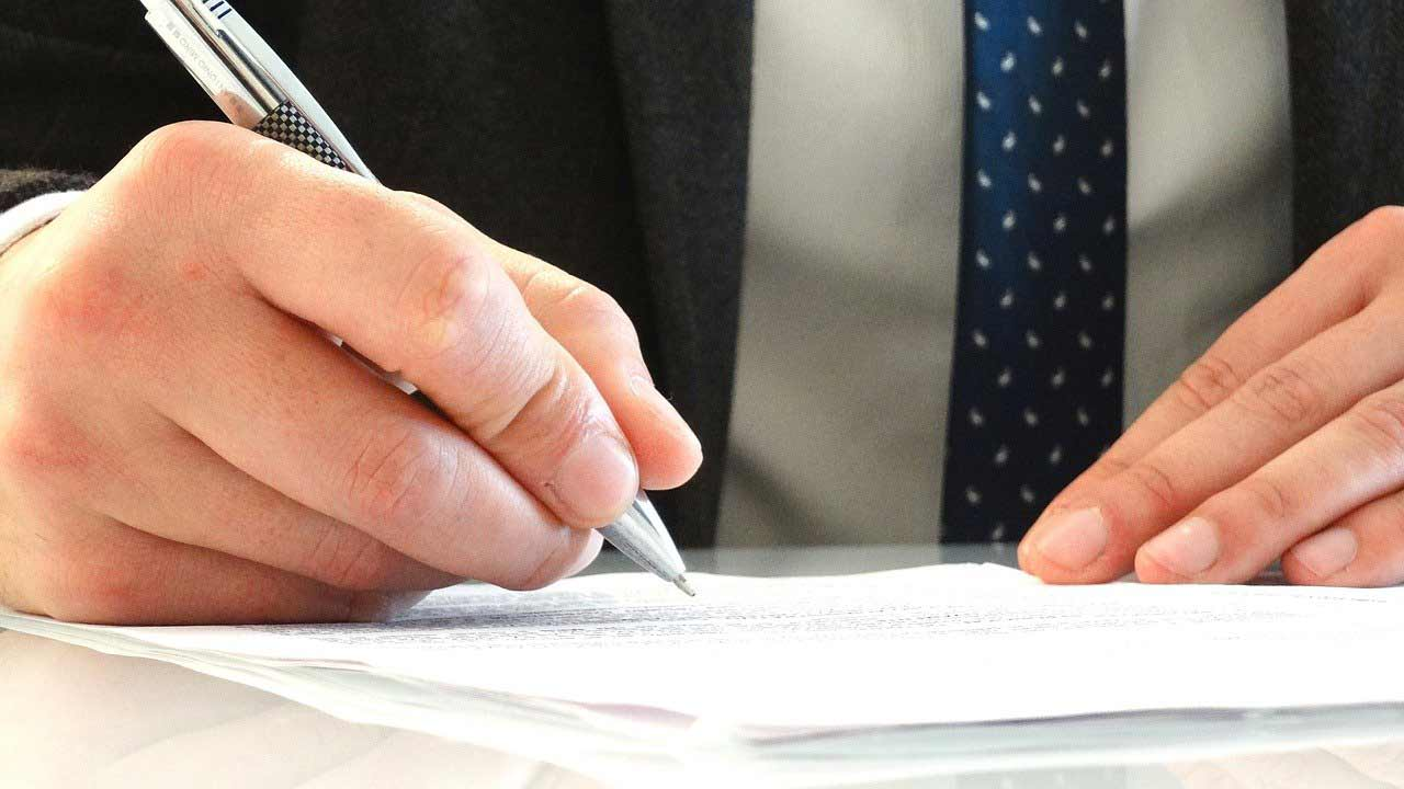 Hands of a man in a suit signing on one of the most important estate planning documents.
