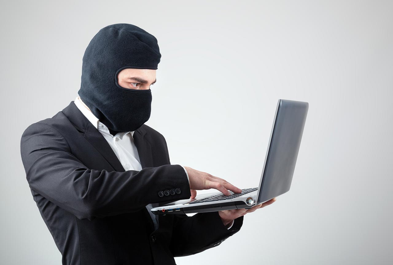 Picture of an employee in a business suit accessing a stolen customer list on his personal laptop.